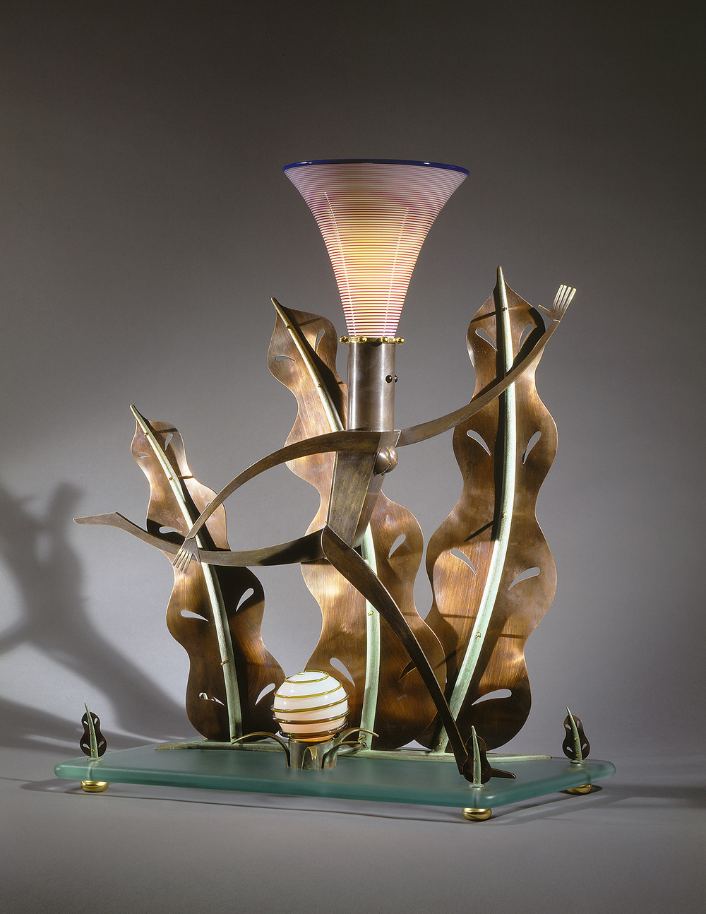 Nude Running among Giant Leaves   1995. Blown glass, bronze, gold-plated bronze, aluminum, plate glass, and lampworked glass. 26 x 29 x 9½""