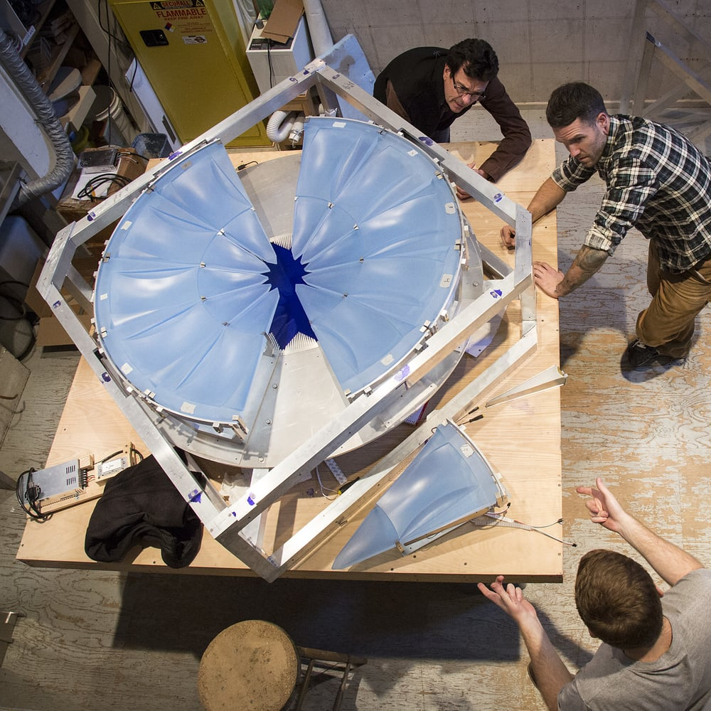 Clockwise from top:  Dan Dailey, Joe Wight, and Dana DiPlacido assemble the glass parts.