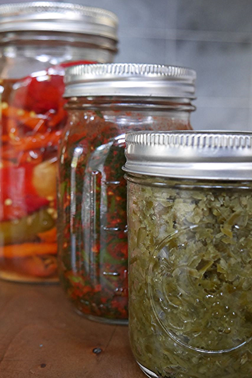 These 3 ferments are each fermenting simply in a jar that is sealed tight and burped daily. From L  to R, brining peppers for hot sauce, nettle kimchi, garlic scape paste.