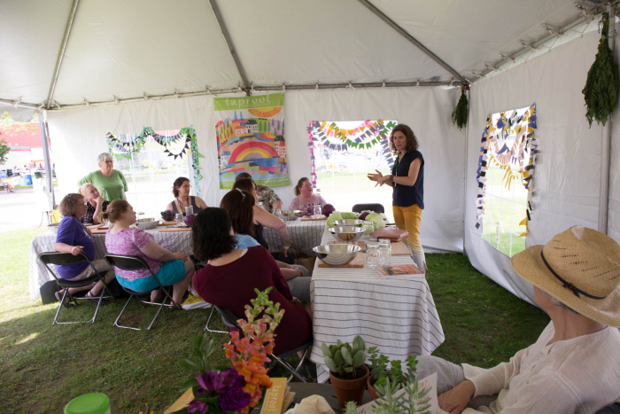 Kirsten taught kraut making to a couple rounds of enthusiastic folks in the Taproot Magazine tent at the Mother Earth News Fair in Vermont . Everyone was so excited to take home their very own jar to tend to on their counter. Photo by Amanda Blake Soule.