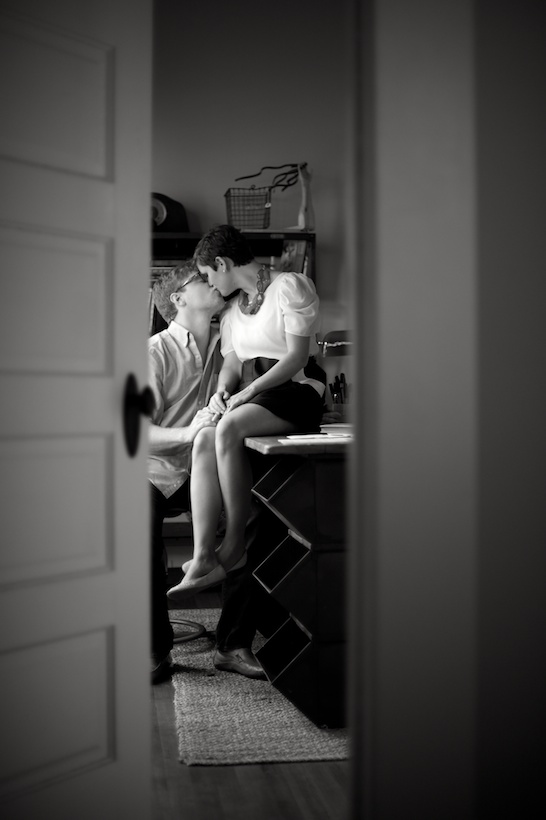Black and white photo by Elizabeth Glessner of Glessner Photography of artist Adam Trest and high school teacher Lily Hedgepeth's engagement session in the office at their historic home in downtown Laurel, Mississippi
