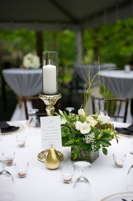 Wedding reception detail photo by Elizabeth Glessner of Glessner Photography of a table setting featuring centerpieces by florist Linda Smith, gold pears, brown chivari chairs, and event design by Nancy Cox of Simply Elegant Occasions at the spring backyard wedding of J.P. Perkins and Katherine Henry in Asheboro, NC