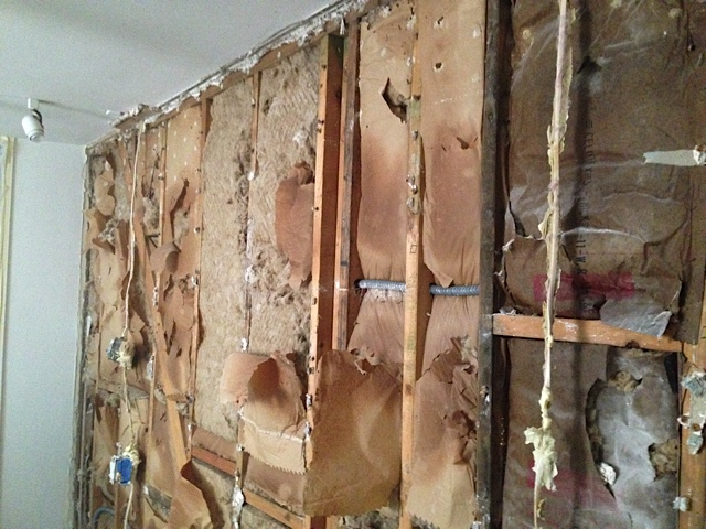 Finally tore down the drywall and plaster on one layer. We see the exposed studs and the insulation.
