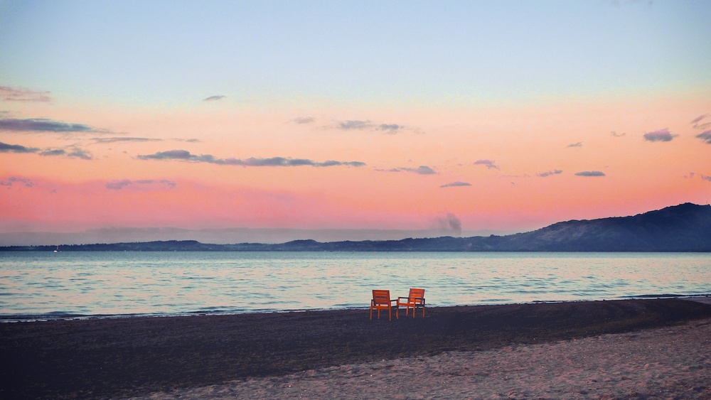 Two empty chairs on the beach during the sunset