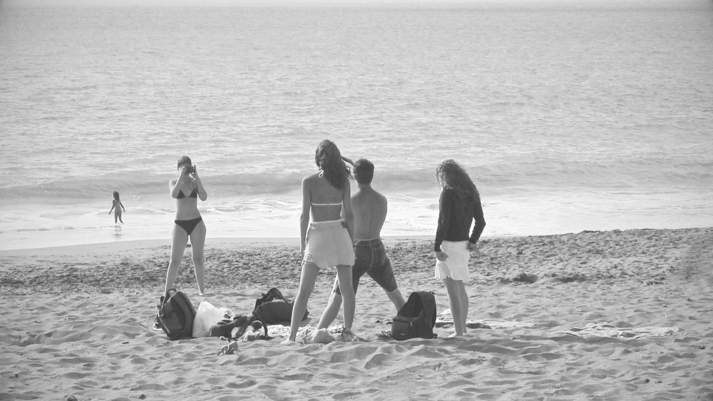 A girl takes a photograph of her friends in a San Francisco beach in 2004