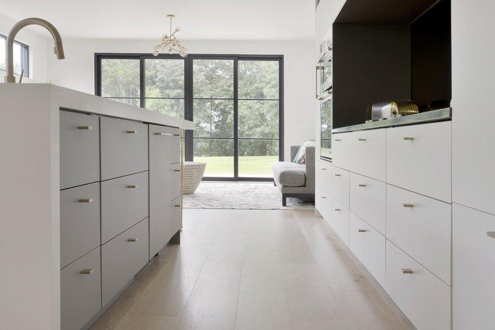 modern kitchen - Warm whites, modern shapes, wide wood planks, light and dark stone, black architectural elements, brass finishes, smart storage systems, functional, elegant design