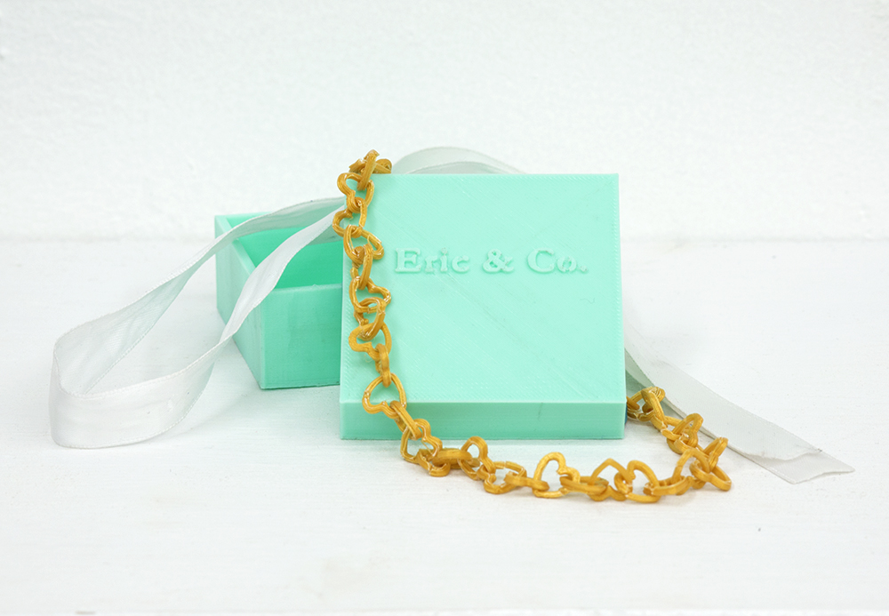 "The 3D printed ""gold"" bracelet is a parody on the commercialization of gestures of romantic affection. Featuring the iconic robin's egg blue of Tiffany's Jewelers, this project plays with ideas of how we determine value."