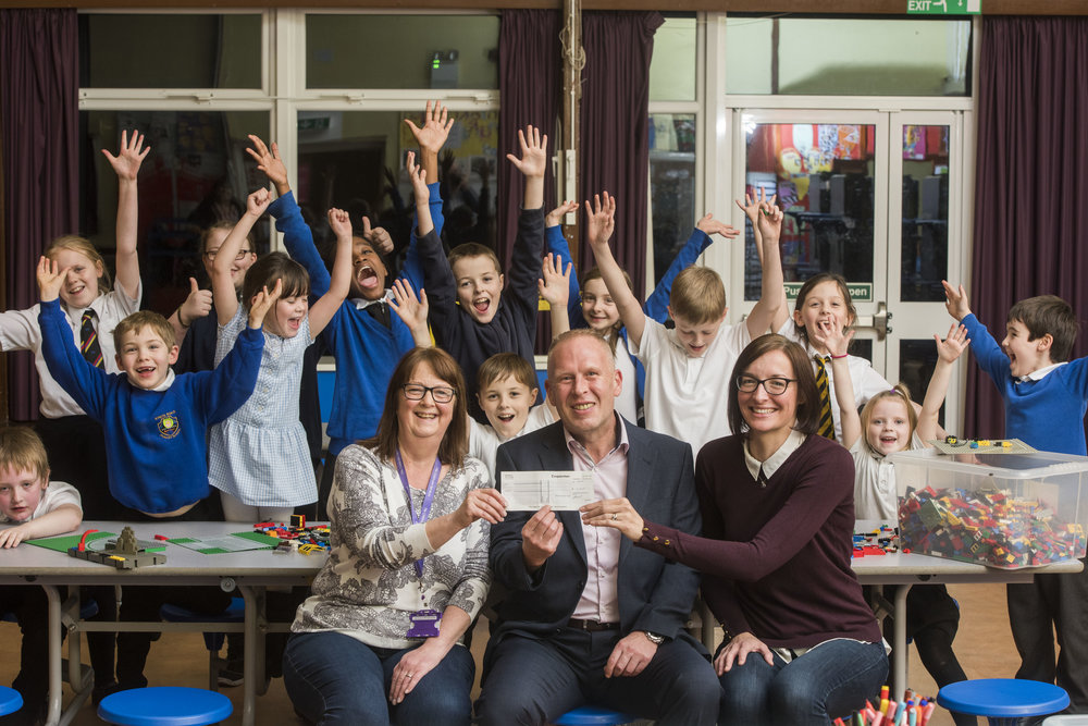 Pictured: Sam Collings from Computershare presents a cheque for £1,000 to help Camdean Primary School purchase after school club equipment. The money was won for the club by mum Tracy McDonald (right) and the cheque was presented to Diane Malcolm Acting Senior (left).