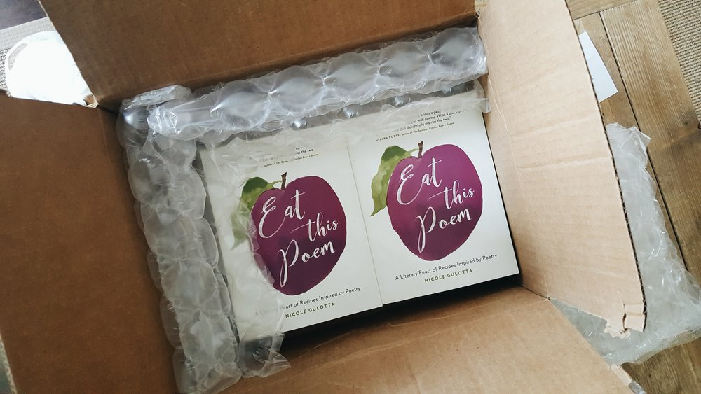 A box of books filled with copies of Eat This Poem