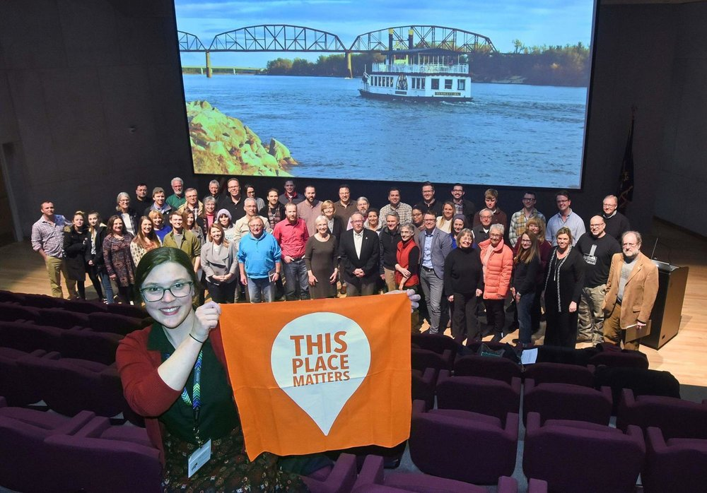 "PND President Emily Sakariassen holds up the National Trust for Historic Preservation's ""This Places Matters"" banner, in a show of support on behalf of grass roots preservation initiatives.Tom Stromme photographer"
