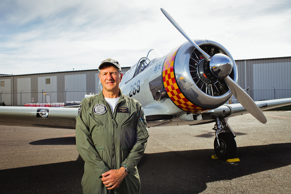 Mark Kandianis stands for a portrait in front of an AT-6, which the Navy designated as the SNJ. Mark will be flying a support cessna during the flight path recreation.