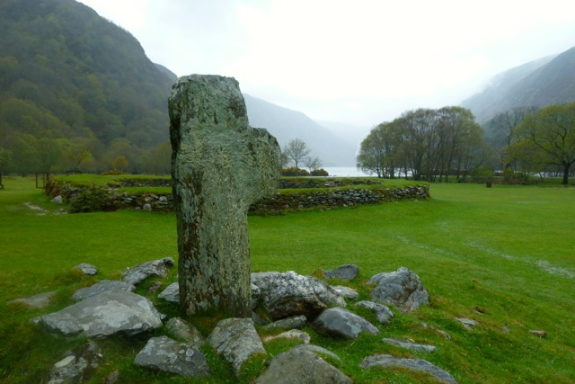 Remnant of a high cross looking toward a round enclosure at the upper lake at Glendalough in Ireland