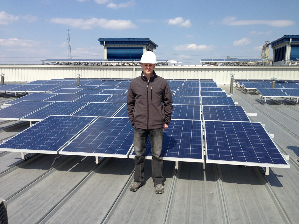 Tipping Point CEO Eric Zimmer in front of a small part of the City of Columbus Fleet Maintenance Building solar array