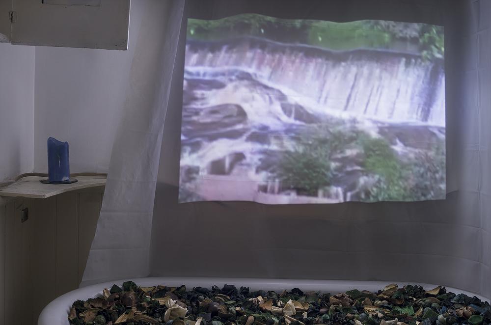 "Shlon's ""Niagara II."" Single channel SD video projection, 5-minute loop. Balara's ""Ocean Breeze."" Potpourri, tub."