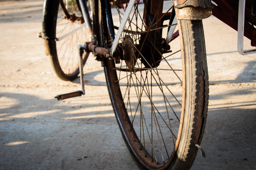 Trishaw drivers, unable to afford new tires, are constantly repairing what they have