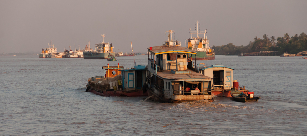 A boat pushes another down the Yangon River