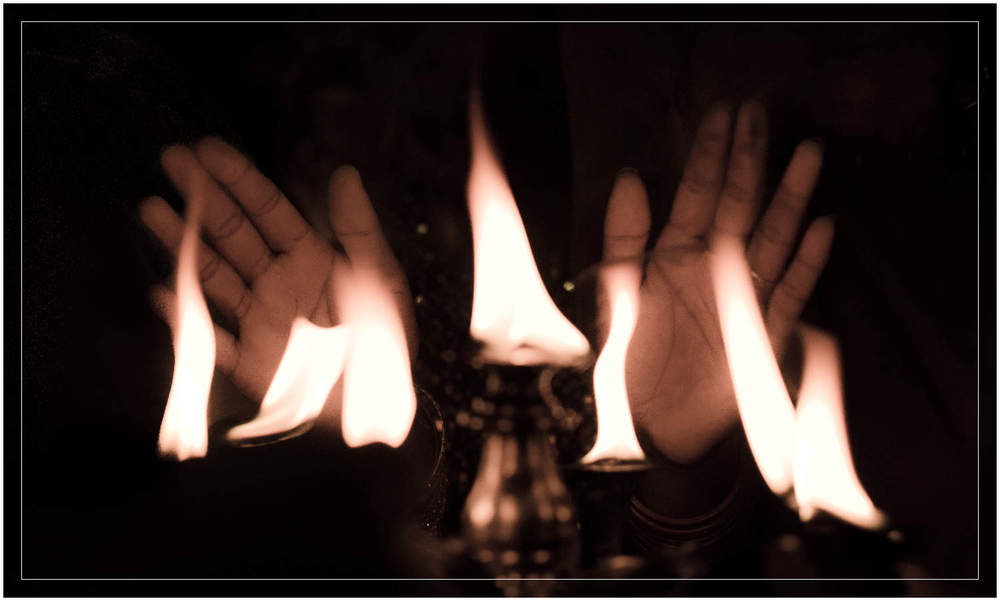 The hands touch the fire before coming back to touch the body in this Hindu ritual.  Yangon - Burma / Myanmar
