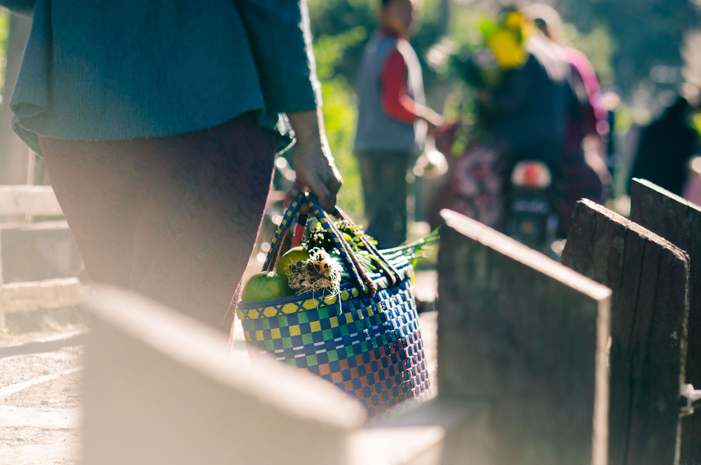 A woman leaves the market with her woven bag full of fresh fruit and vegetables. Kalaw, Burma / Myanmar