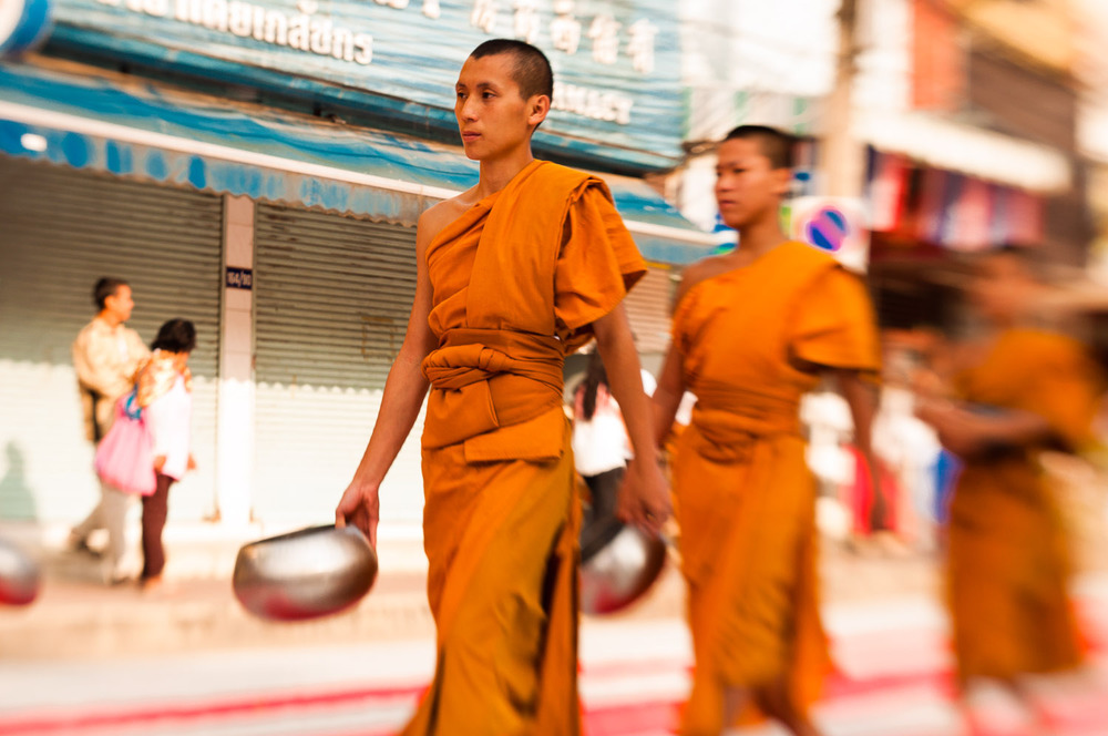Monks walk down the street at the conclusion of a giant gathering in Chiang Mai, Thailand.