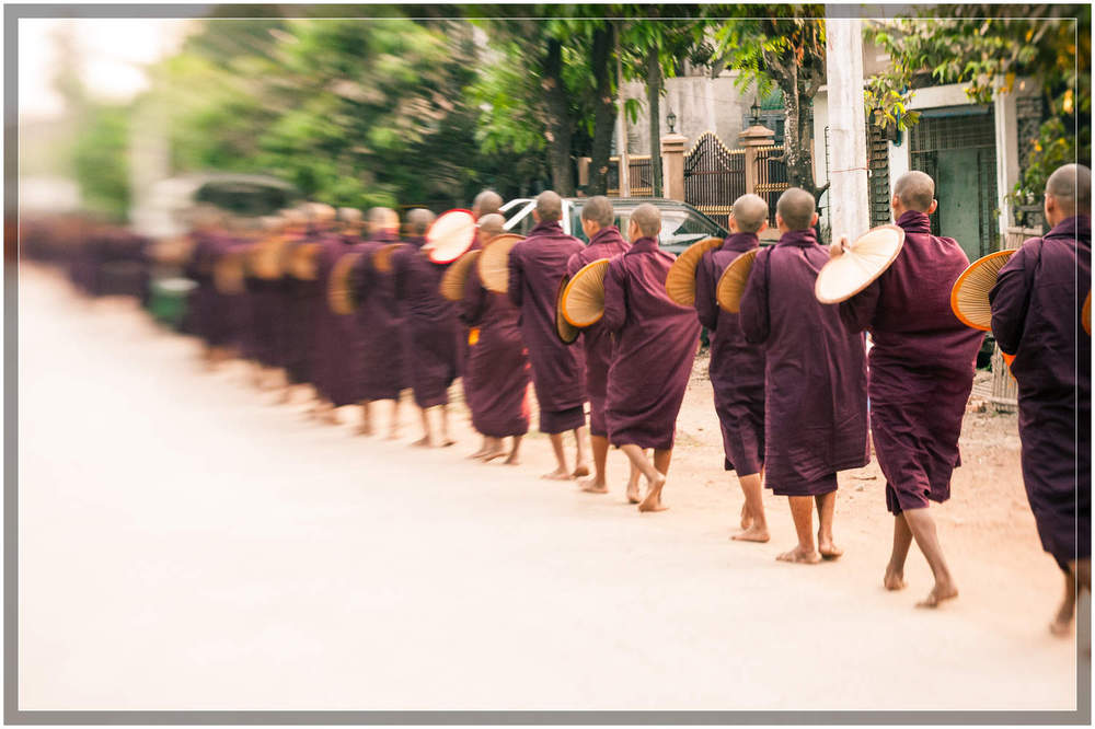 Monks form a line walking down the street in the town of Mawlamyine, a port city in south-eastern Myanmar (Burma)   © Dustin Main 2013