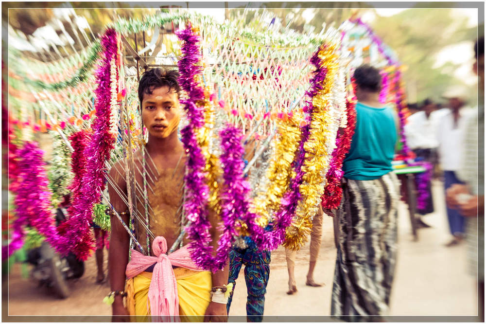 A Hindu devotee, decorated and pierced, makes the pilgrimage to the temple in the streets of Myanmar's third largest city, Mawlamyine.  © Dustin Main 2013