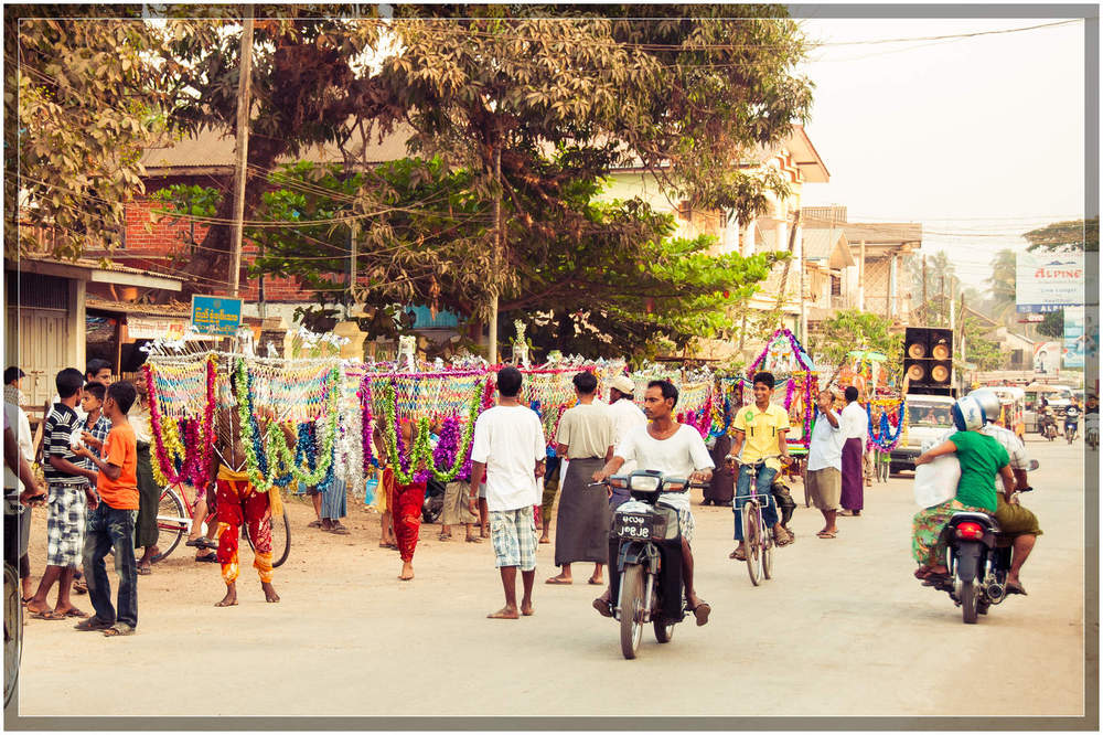 The procession moves along a main street in Mawlamyine.  On the opposite side of the street (out of frame), Buddhist monks walk in the opposite direction.   © Dustin Main