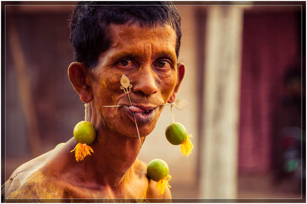 A devotee with his tongue and cheeks pierced slowly makes his way towards the temple in Mawlamyine. © Dustin Main 2013