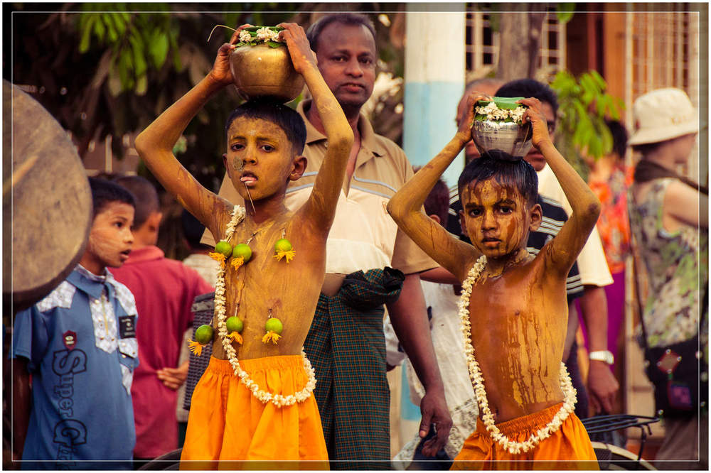 Children carry pots on their heads to show their devotion.  One child has lime fruit hanging from hooks in his flesh and a skewer in his tongue. © Dustin Main 2013