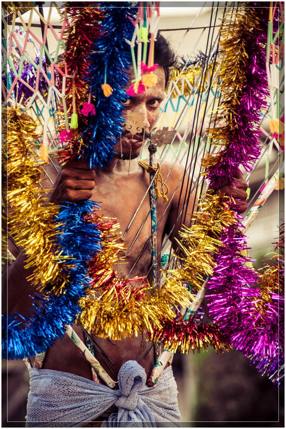 A devotee carrying a vel kavadi (burden) made of metal spears piercing his torso, with a decorated canopy overtop.  The tongue is pierced to be a constant reminder of god.  © Dustin Main 2013