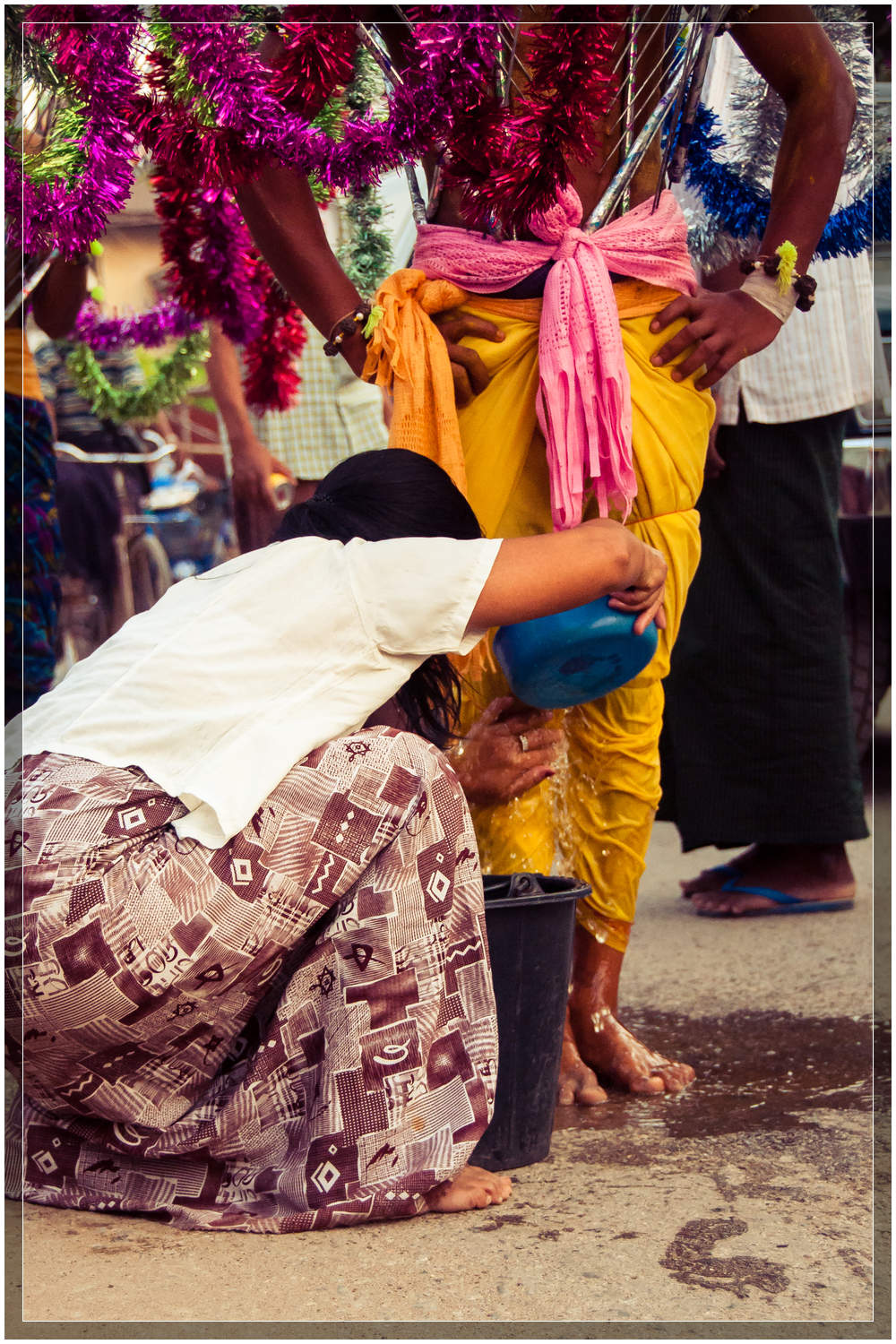A woman washes the feet of each of the devotees as they pass along the street during the procession in Mawlamyine, Myanmar (Burma). © Dustin Main 2013