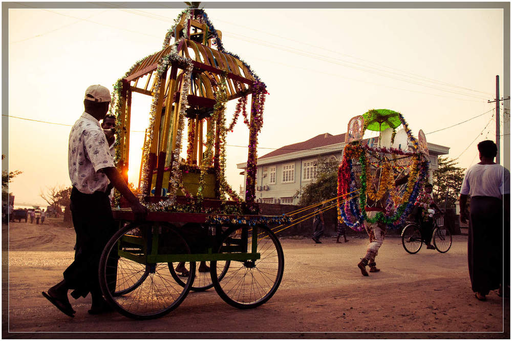 The devotee pulls the carriage down the road as the sun sets in Mawlamyine. © Dustin Main 2013