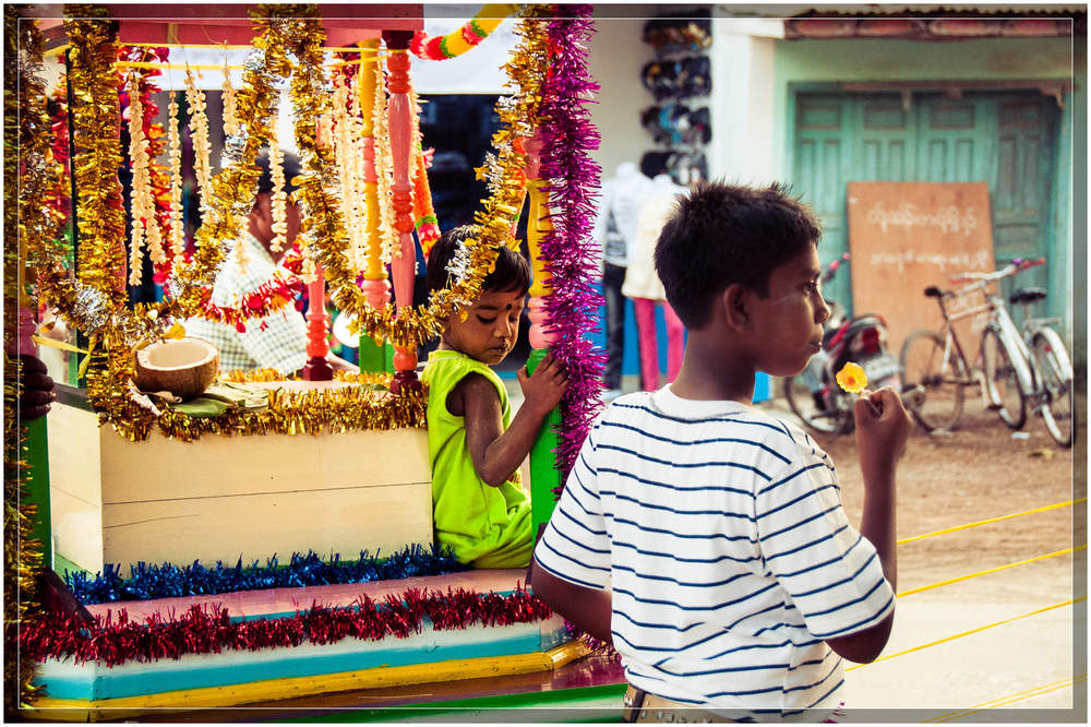 A child rides atop a carriage being pulled by a devotee in this Hindu ceremony.  © Dustin Main 2013