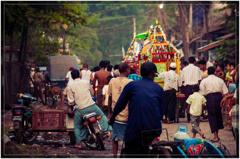 The procession continues down a side street en route to the temple.  While comprising mostly of Buddhists, Myanmar (Burma) is home to people practicing many religions including sizable Christian and Hindu populations.  © Dustin Main 2013