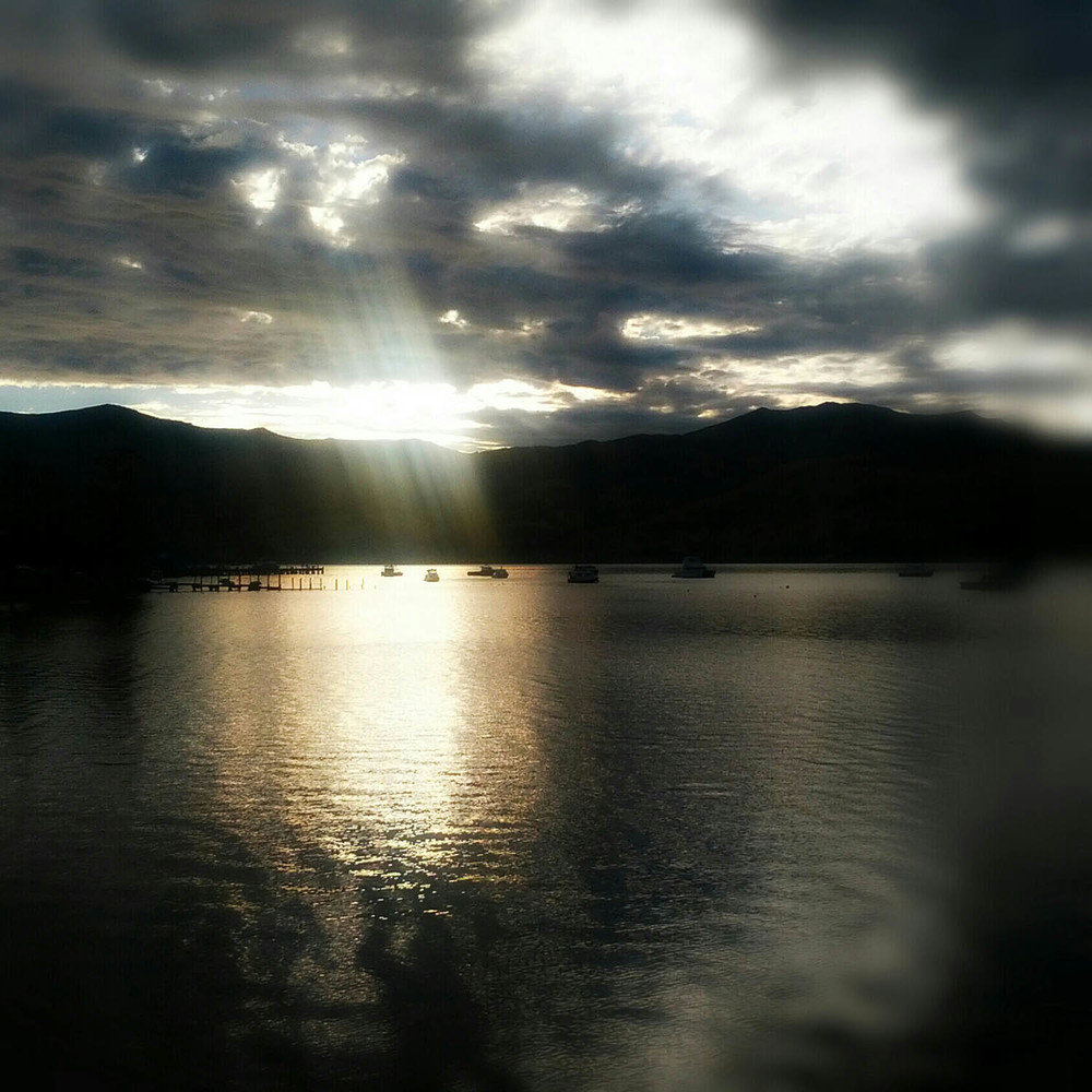 The last bit of the sun drops in to Akaroa harbour at sunset.