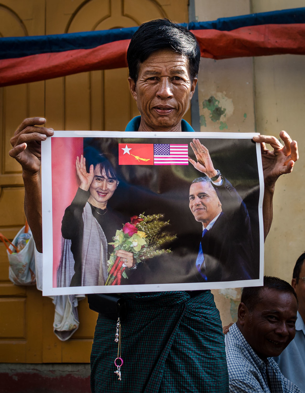 A local taxi driver shows his new poster of Aung San Suu Kyi and Barack Obama the day after his historic trip to Yangon in November 2012.