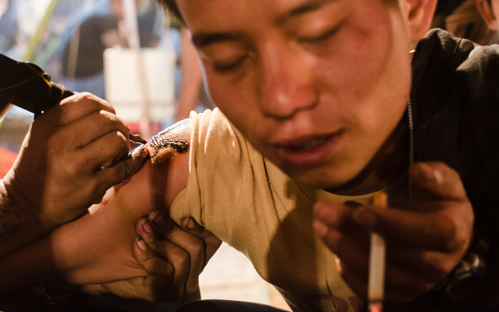 A young Shan man gets a tattoo at the annual Pindaya Shwe Oo Min Festival in March.  The tattoo cost him roughly $2.50 and took about 2 minutes. © Dustin Main 2013