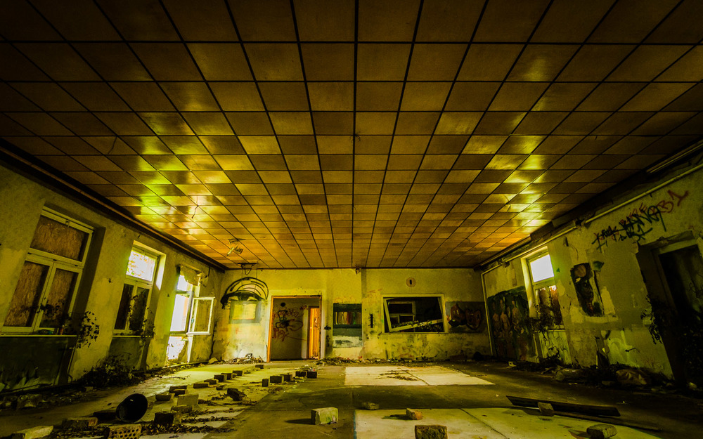 The eerie, filtered light from outside colors the walls of an abandoned building in Berlin, Germany.  © Dustin Main 2013