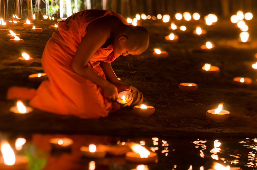 A young monk lights a candle, creating a dream-like world for the Visakha Bucha Buddhist holiday.  Chiang Mai, Thailand. © Dustin Main 2013