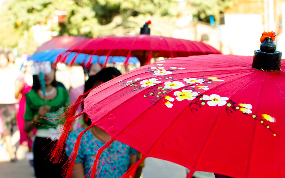 Beautiful and bright parasols provide both shade and a dose of style for the women in the procession.  Nyaung U (Bagan), Myanmar / Burma  © Dustin Main 2014