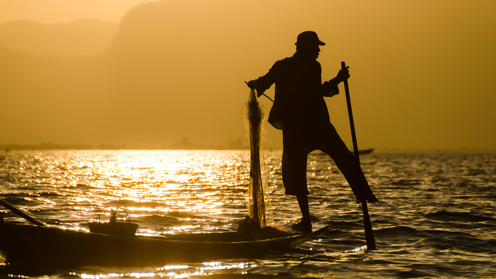 A fisherman plays out a balancing act on his canoe while he lets out line for his next catch © Dustin Main 2014