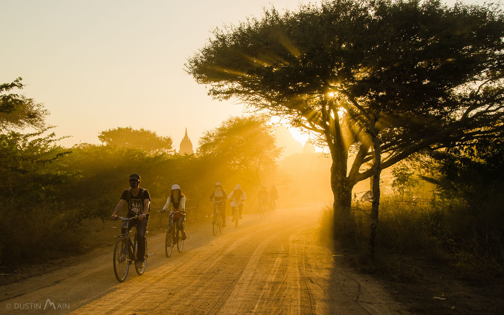 Cyclists  traveling through the dusty roads of Bagan as dusk nears. © Dustin Main 2014