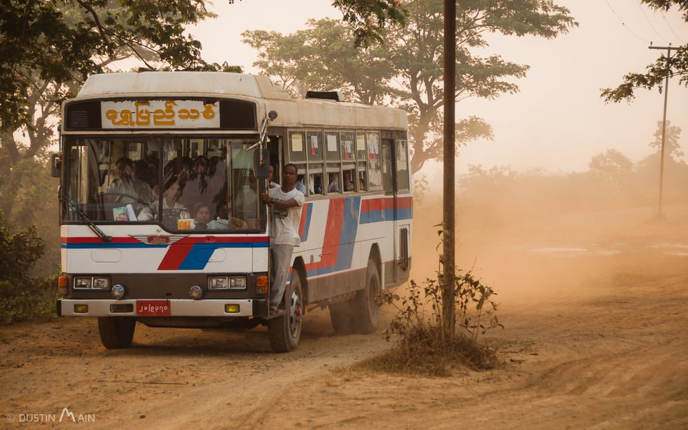 A packed local bus barrels down the dusty road in rural Rakhine State, Myanmar. © Dustin Main 2012