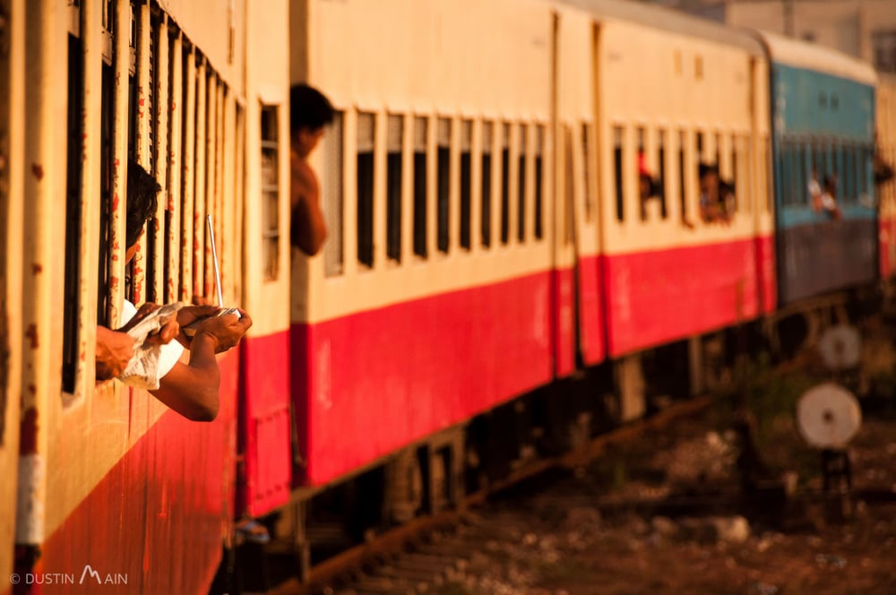 Tuning a radio and harnessing the natural air conditioning on a train journey in southern Myanmar. © Dustin Main 2013