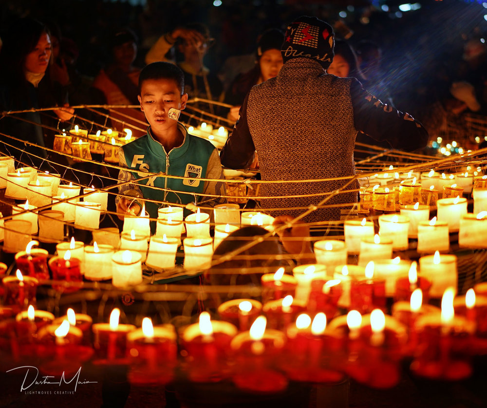 A young boy lights candles for the Sein Na Pan fire balloon near Taunggyi, Shan State.  © Dustin Main 2016