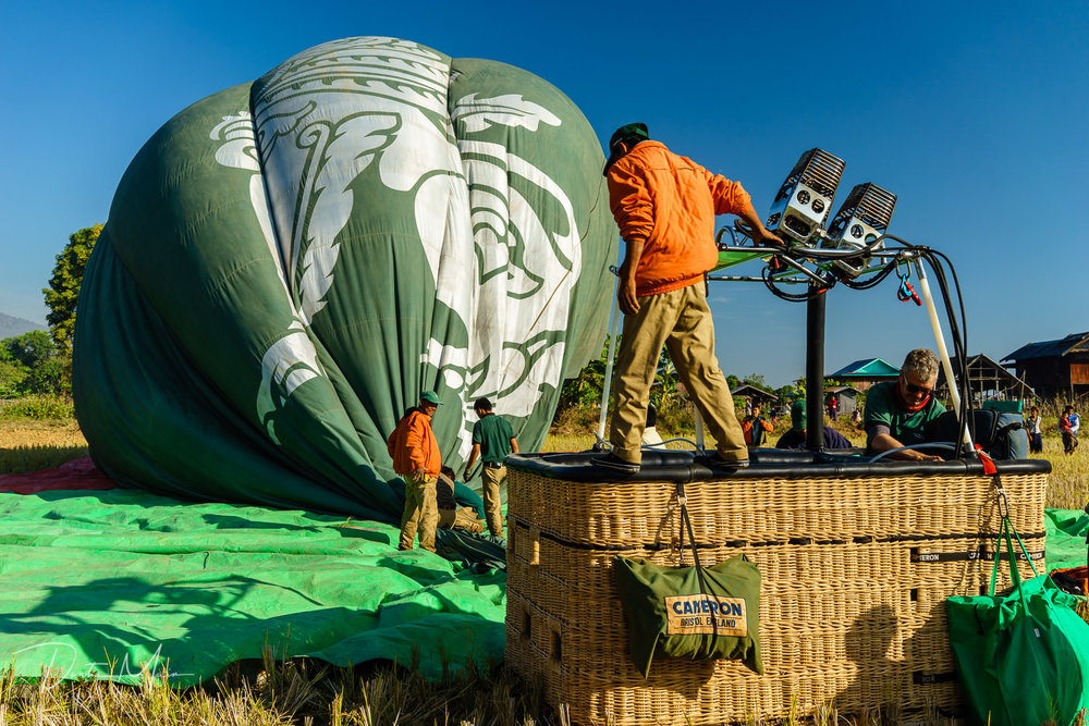 The ground crew begins the process of packing up the hot air balloon and basket before heading back to Nyaungshwe.  © Dustin Main 2017