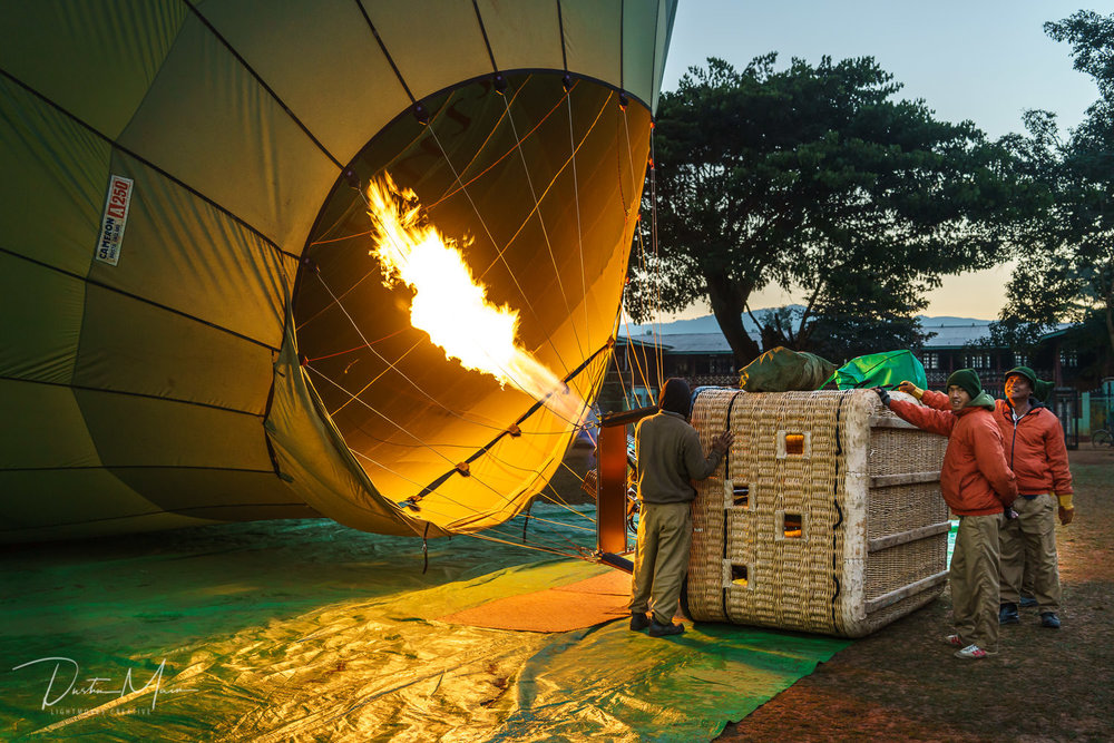 The crew fires up the burners to fill the balloon with hot air.  Minutes later, we were in the sky above Inle Lake.  © Dustin Main 2017