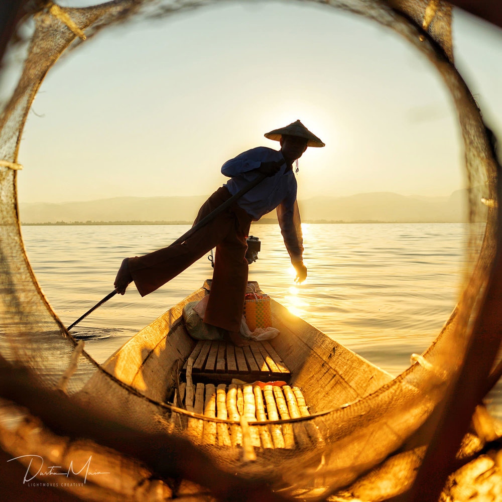 Intha fisherman balances on one foot as he rows across the shallow Inle Lake. © Dustin Main 2018