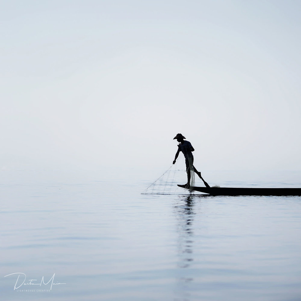 Silhouette of an Intha Fisherman on Inle Lake through the haze shortly after sunrise. © Dustin Main 2018