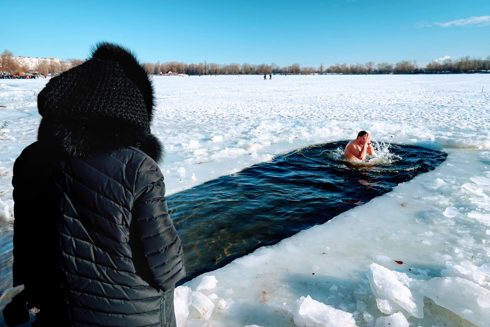 Warmly dressed woman watches a man swim in the frigid waters of the Dnieper river. © Dustin Main 2019