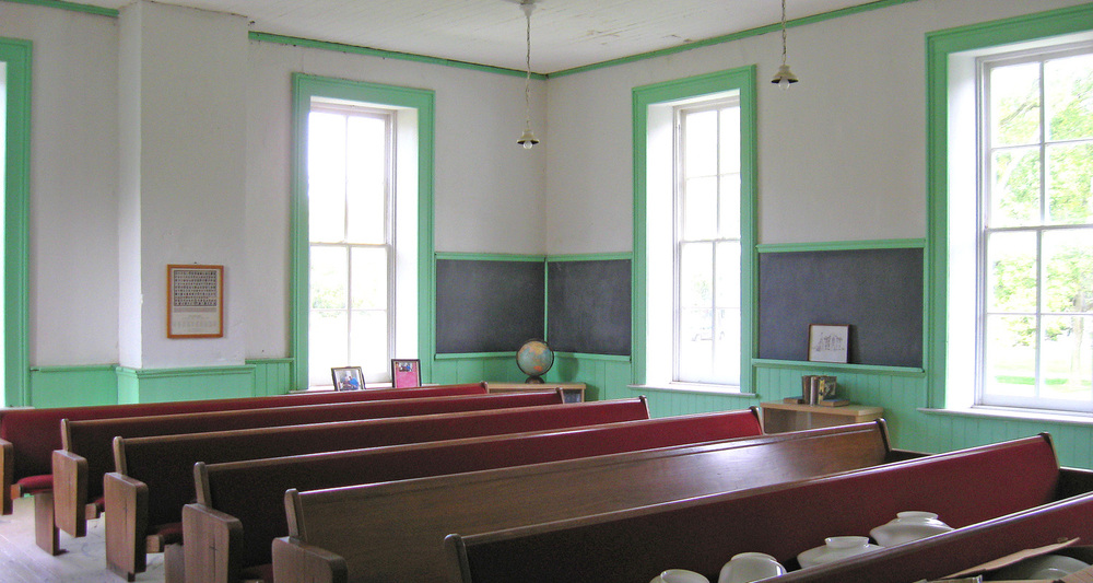 School room inside with pew style seating.  Note that the hanging light globes are in the process of being replaced.